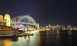 Sydney Harbour nattetidpanorama med bron i norr Sydney Royaltyfri Foto