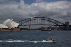 Sydney Harbour och att visa operahuset och bron med hastighetsfartyget i forground royaltyfri foto