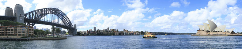 Sydney Harbour panorama. Harbour bridge and opera house Sydney with ferry in middle. Panorama from The Rocks stock images
