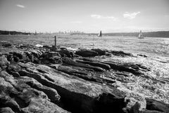 Sydney harbour skyline. Picture taken on top of some rocks in Watson bay, in the photo appears the harbour of Sydney, Australia, and some sailing boats Royalty Free Stock Photography