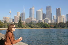 Sydney skyline and bay with young woman. A young woman overlooks the famous Farm Cove Bay - with its Botanic Gardens and Sydney skyline in the background Royalty Free Stock Photography
