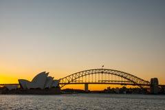 Sydney-Juni 2009: Solnedgången på operahuset och Habour överbryggar landm arkivbilder