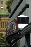 Sydney monorail. Train on single rail, buildings in background, telephoto Stock Photo