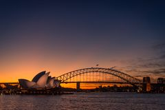 Sydney, New South Wales / Australia - May 17th 2016: Sydney Opera House lit up with light at night time with Harbour Bridge to the. Right and the last red and royalty free stock photography