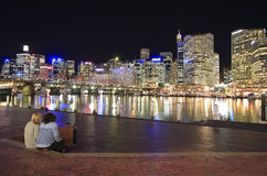 Sydney at Night. A view of a couple watching Sydney at night from Darling Harbour Royalty Free Stock Photography