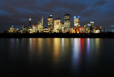 Sydney at night. Sydney cbd panorama at night, buildings reflection in water, dark cloudy night sky Royalty Free Stock Photo
