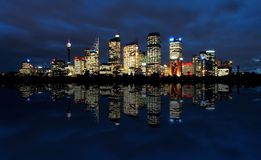 Sydney at night. Sydney cbd panorama at night, buildings reflection in water, dark cloudy night sky Stock Photos