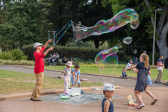 Bubbles at Hyde Park. SYDNEY,NSW,AUSTRALIA-NOVEMBER 20,2016: Street artist with bubble wand and massive rainbow bubbles with kids in Hyde Park in Sydney Royalty Free Stock Image