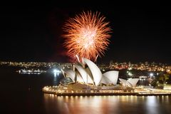 Sydney Opera House and brilliant fireworks show illuminating the harbor with fiery orange light. Sydney, Australia - March 8, 2018 - Orange explosion of stock image