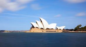 Sydney Opera House com água e as nuvens obscuras foto de stock royalty free