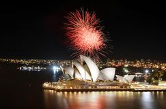 The Sydney Opera House hosts an incredible fireworks show with reflections on the harbor. Sydney, Australia - March 8, 2018 - Fiery red fireworks light up the royalty free stock photo