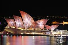 Sydney Opera House iluminou-se com cores vibrantes e testes padrões durante Imagens de Stock