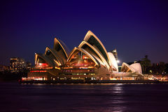 Sydney Opera House. At night with city lights in the background and Sydney Harbour in the foreground Stock Photography