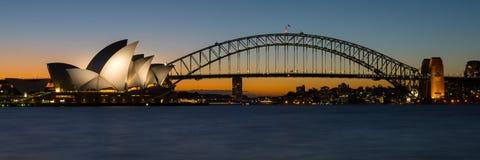 Sydney Opera House och hamnbron på solnedgången Arkivbild