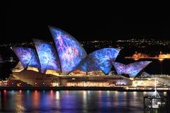 Sydney Opera House som är upplyst i visuell färg livliga Sydney Arkivfoto