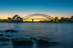 Sydney Opera House at sunset. Sydney, Australia - July 03, 2016: Panoramic view of Sydney Opera House and Sydney Harbour Bridge along Sydney Harbour at dusk royalty free stock photography