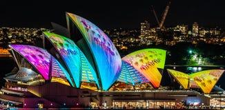 Sydney Opera House tände upp på natten på den nära livliga ljusa festivalen - upp royaltyfri fotografi