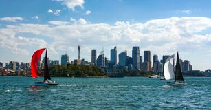 Sydney`s iconic skyline is framed between two colorful sailboats sailing the city`s beautiful harbor Royalty Free Stock Image