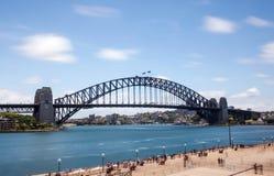 Sydney schronienia most z rozmytymi chmurami i wodą Zdjęcia Stock