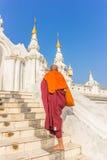 Sydostliga asiatiska unga buddistiska munkar som går morgonallmosa i Inl Arkivfoto