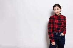 年轻sylish行家女孩佩带的红色检查了握她的在口袋的衬衣和牛仔裤手有站立ne的愉快的表示 库存照片