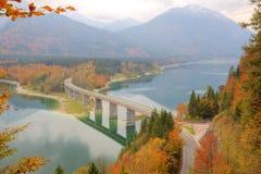 横渡在有美好的反射的湖Sylvenstein的一座弯曲的桥梁在水 免版税图库摄影