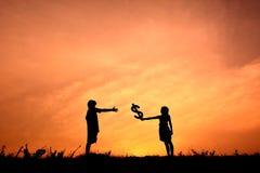 Sylwetek dzieci trzyma pieniądze Obraz Royalty Free