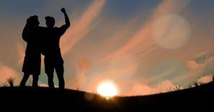 Sylwetek ludzie świętuje zwycięstwo przeciw niebu podczas zmierzchu Zdjęcia Stock