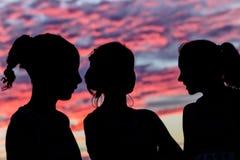 Sylwetek młodych kobiet rozmowy powstającego słońca ranek Obrazy Royalty Free
