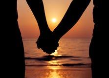 Sylwetek pary trzyma ręki