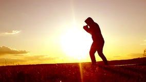 Sylwetka ćwiczy tajlandzkiego boks mężczyzna Sylwetka sztuki samoobrony obsługuje stażowego boks na plaży nad pięknym zmierzchu b