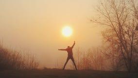 Sylwetka śmieszny szalony mężczyzny taniec przeciw wschód słońca lub zmierzchowi Pomyślny radosny i rozochocony mężczyzny taniec  zbiory