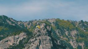Sylwetka żółty paraglider latanie przeciw niebu zdjęcie wideo