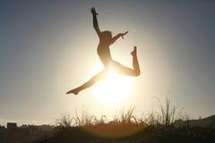 Sylwetka akrobatyczny nastoletni gimnastyczki doskakiwanie z słońcem behind Obrazy Royalty Free