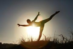Sylwetka akrobatyczny nastoletni gimnastyczki równoważenie z słońca behi Zdjęcia Royalty Free