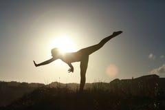 Sylwetka akrobatyczny nastoletni gimnastyczki równoważenie z słońca behi Obraz Royalty Free