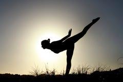 Sylwetka akrobatyczny nastoletni gimnastyczki równoważenie z słońca behi Zdjęcia Stock