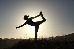 Sylwetka akrobatyczny nastoletni gimnastyczki równoważenie z słońca behi Obrazy Stock
