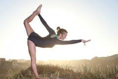 Sylwetka akrobatyczny nastoletni gimnastyczki równoważenie z słońca behi Fotografia Stock