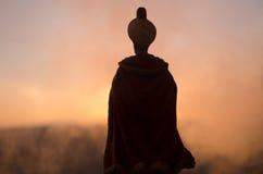 Sylwetka Arabski mężczyzna stoi samotnie w pustyni i oglądać zmierzch z chmurami mgła Wschodnia bajka Fotografia Royalty Free