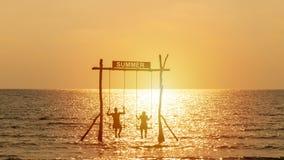 Sylwetka bawić się huśtawkę nad morzem z lato znakiem szczęśliwa para Szcz??liwy wakacje poj?cie obraz royalty free