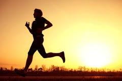 Sylwetka biegacz w zmierzchu wzroscie Zdjęcia Royalty Free