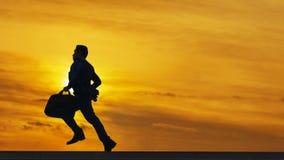 Sylwetka biznesowy mężczyzna biega z laptop teczką przy pieszy obraz stock