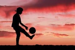 Sylwetka chłopiec bawić się futbol lub piłkę nożną przy Fotografia Stock