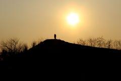 Sylwetka chłopiec i dziewczyny gapi się przy słońcem Zdjęcia Royalty Free