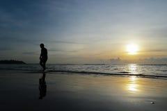 Sylwetka chłopiec odprowadzenie na plaży przy zmierzchu tłem Zdjęcia Stock
