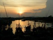 Sylwetka cumownicze łodzie rybackie na rzece z oszałamiająco zmierzchem Zdjęcia Stock
