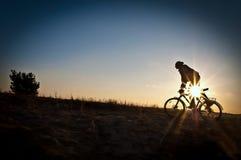 Sylwetka cyklista prędkości jazda na zmierzchu zdjęcie stock