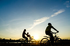 Sylwetka cyklista z dziecko ruchem na zmierzchu tle Obraz Royalty Free