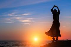 Sylwetka dancingowa kobieta na dennym wybrzeżu podczas zmierzchu Zdjęcie Royalty Free